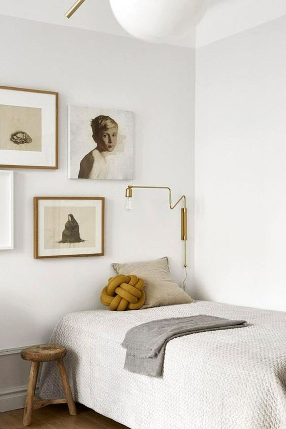 Soverom med pent dekket seng, gammel krakk og kunst på veggen.