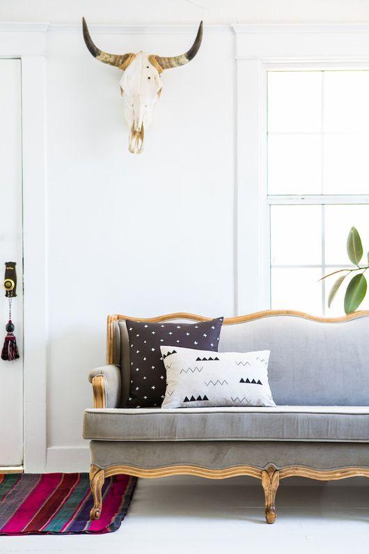 vilthode på veggen bak en grå sofa med løveføtter